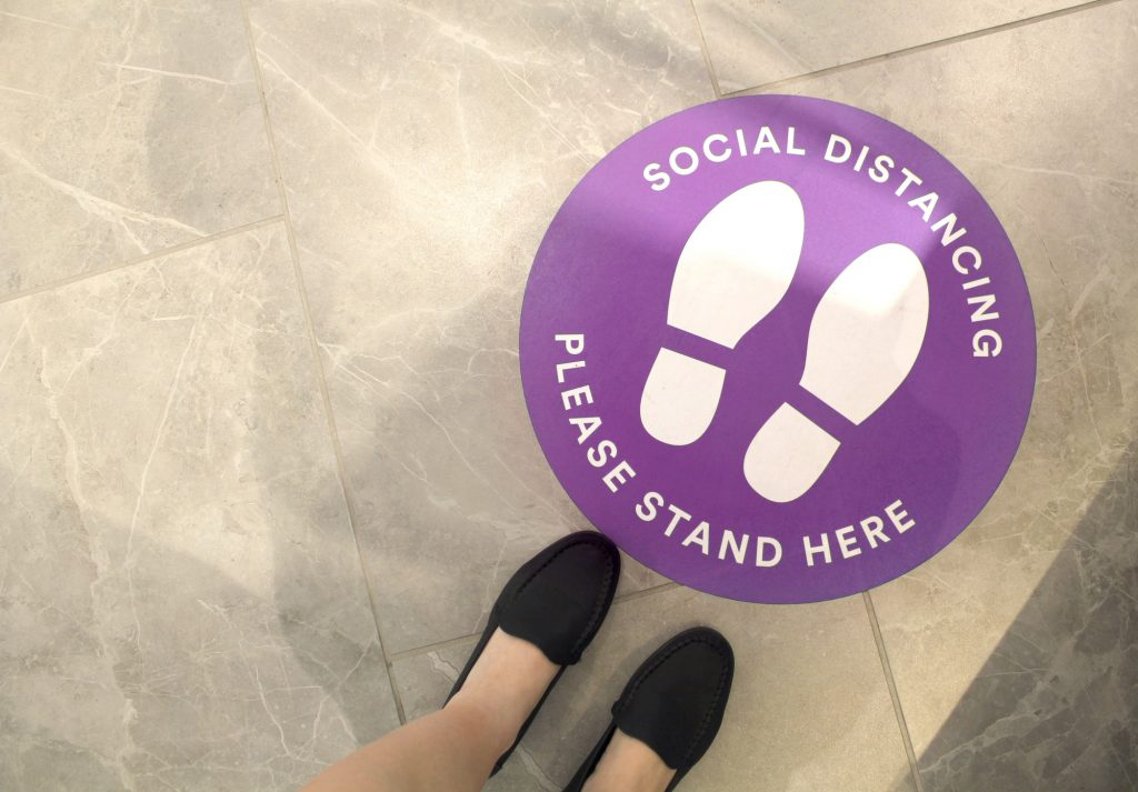 Purple social distancing sign on the floor